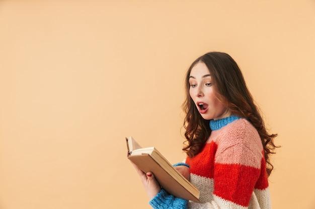 Immagine di una donna intelligente 20s con i capelli lunghi sorridente e leggendo il libro, in piedi isolato