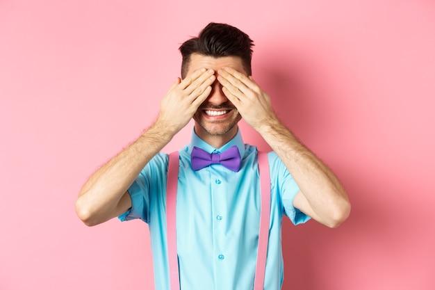 Immagine del bel ragazzo sorridente in attesa di sorpresa con gli occhi chiusi, in piedi in abito di fantasia su sfondo rosa.