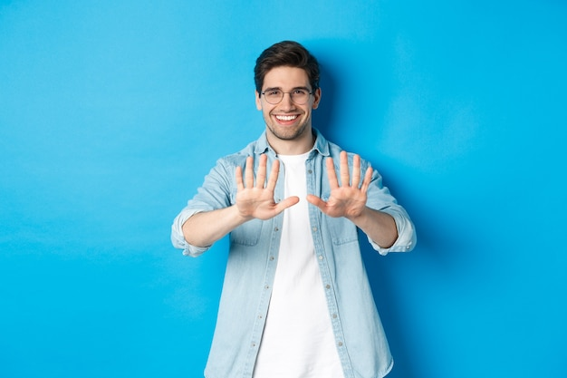 Immagine di un uomo sorridente che guarda soddisfatto della sua manicure, visita il salone di bellezza, in piedi sul muro blu