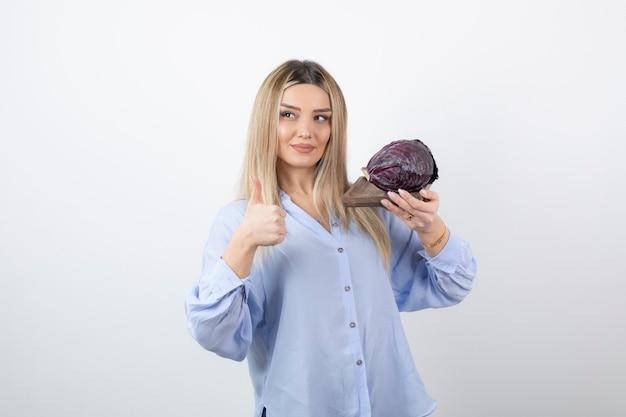 Immagine di un modello sorridente della donna graziosa con il cavolo che mostra un pollice in su.