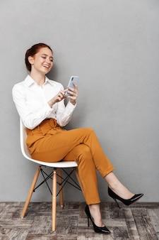 Immagine di una donna d'affari dai capelli rossi sorridente 20s in abbigliamento formale utilizzando il telefono cellulare mentre è seduto su una sedia in ufficio isolato su gray