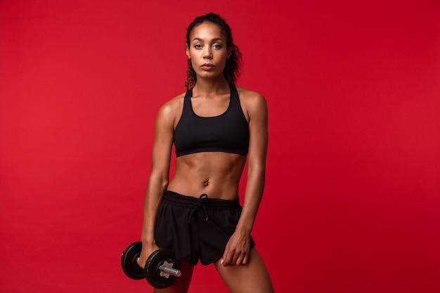 Immagine della donna afroamericana sportiva in abiti sportivi neri che solleva il manubrio, isolato sopra la parete rossa