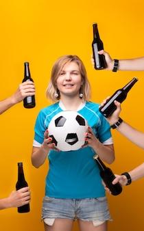 Immagine della bionda sportiva con la scelta tra palla e bottiglia di alcol su sfondo arancione