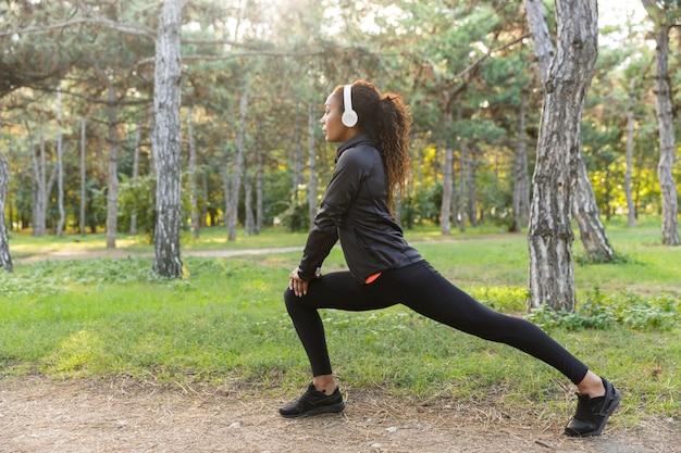 Immagine di una sportiva 20s che indossa tuta nera che si allena e che allunga il corpo nel parco verde