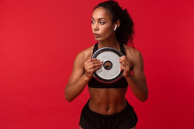 Immagine della donna afroamericana sportiva in abbigliamento sportivo nero che tiene bilanciere, isolato sopra la parete rossa