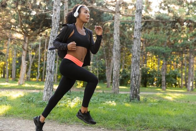 Immagine di una donna sportiva 20s che indossa tuta nera e cuffie che lavorano, mentre corre attraverso il parco verde
