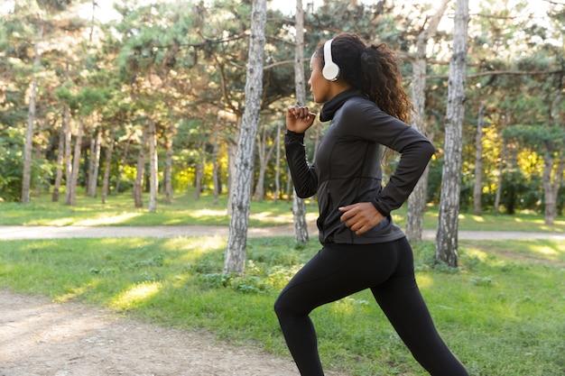 Immagine di una donna forte di 20 anni che indossa una tuta nera e le cuffie che lavorano, mentre attraversa il parco verde