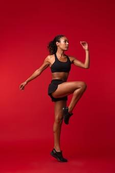 L'immagine di una forte giovane donna africana di sport fitness in posa isolata sopra la parete rossa della parete fa esercizi.