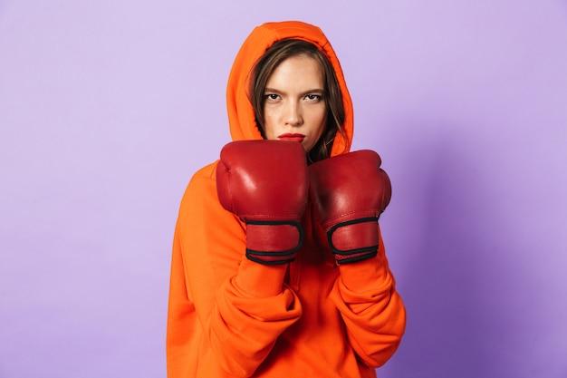 Immagine di un forte pugile giovane donna in posa isolato su muro viola muro indossando guanti da boxe.