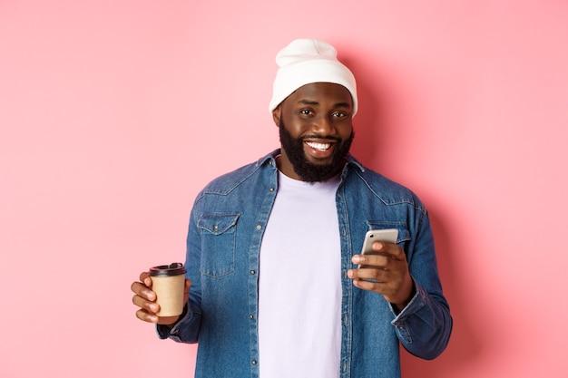 Immagine di un elegante hipster nero che beve caffè da asporto, legge un messaggio al telefono e sorride, in piedi su sfondo rosa.