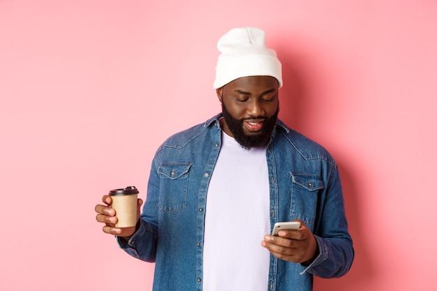 Immagine di un elegante hipster nero che beve caffè da asporto, legge un messaggio sul telefono, in piedi su sfondo rosa.