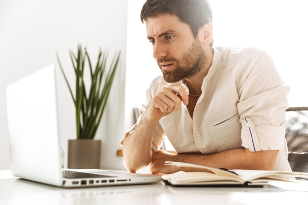Immagine di uomo d'affari di successo anni '30 che indossa una camicia bianca che lavora con laptop e documenti cartacei, mentre è seduto in ufficio luminoso