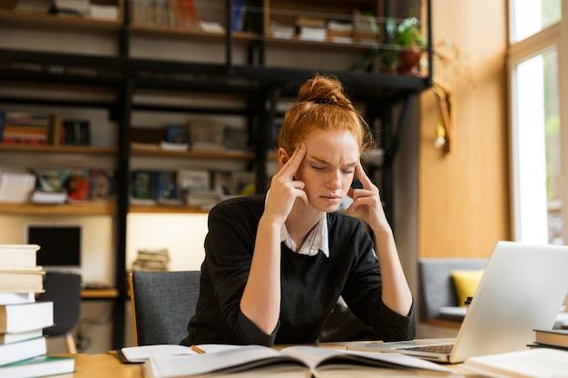 Immagine di tesa donna concentrata studiando, mentre è seduto alla scrivania nella biblioteca del college con la parete dello scaffale