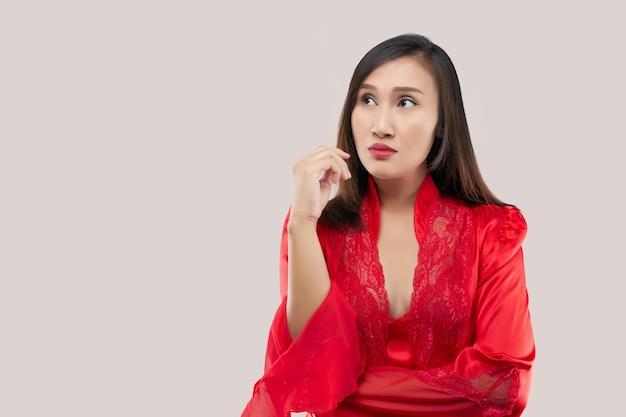Immagine di pensiero sexy signora in piedi isolato su sfondo rosa. distogliere lo sguardo. la mano vicino al viso e alla bocca. donna asiatica in un indumenti da letto di raso rosso che indossa il pensiero di veste di pizzo guarda a sinistra.