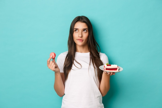Immagine della donna castana premurosa, che fa scelta tra dessert, che tiene amaretto e torta