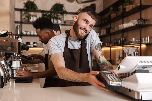Immagine di tre colleghi uomini di caffè felici nel bar caffetteria che lavorano al chiuso parlando al telefono cellulare.