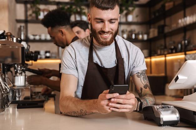 Immagine di tre colleghi di uomini caffè felici nel bar caffetteria che lavorano al chiuso utilizzando il telefono cellulare.
