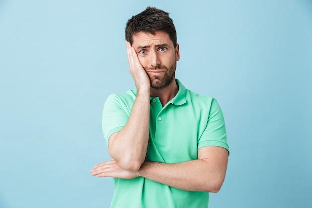 Immagine di giovane uomo barbuto bello annoiato stanco che posa isolato sopra la parete blu.