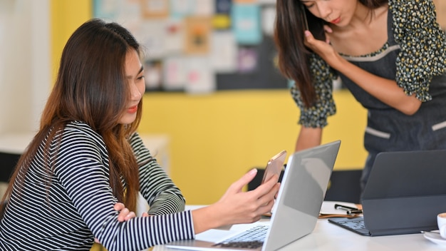 Immagine di due studentesse universitarie che lavorano insieme al computer portatile e al tablet della caffetteria sul tavolo