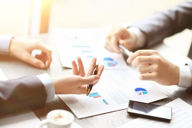Immagine di due giovani uomini d'affari che discutono di un documento alla riunione