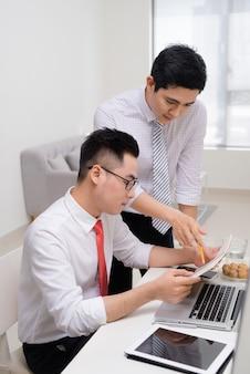 Immagine di due giovani uomini d'affari che interagiscono alla riunione in ufficio