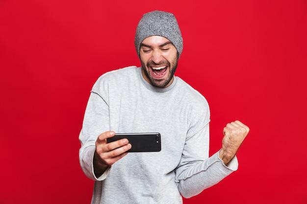 Immagine dell'uomo non rasato 30s che tiene smartphone e che gioca ai videogiochi, isolata