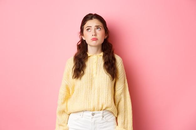 Immagine di sconvolto e cupo giovane donna che tira la faccia triste guardando in alto con rimpianto o gelosia in piedi deluso contro il muro rosa