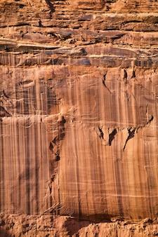 Immagine del dettaglio verticale della trama di una parete rocciosa in pietra con segni verticali
