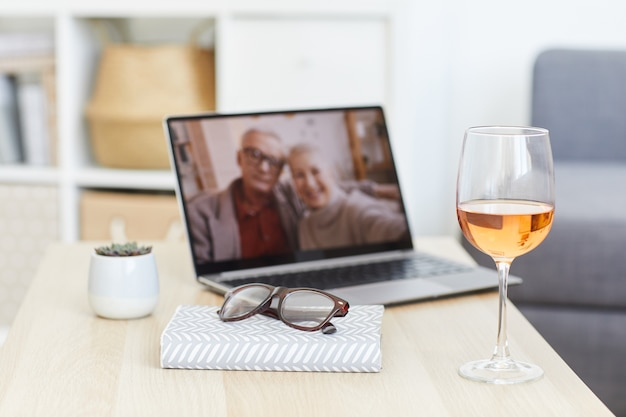 Immagine del bicchiere di vino e blocco note sul tavolo con foto di coppia senior sul monitor del portatile in background nella stanza