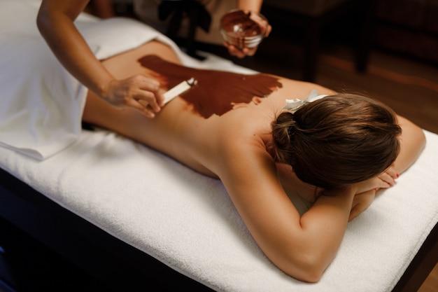 Immagine con la schiena di una ragazza che viene massaggiata e ricoperta di cioccolato