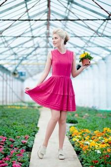 Immagine con una bella ragazza bionda che cammina in giardino