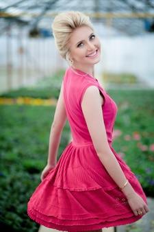 Immagine con una ragazza bionda sorridente, vestita con un abito rosa