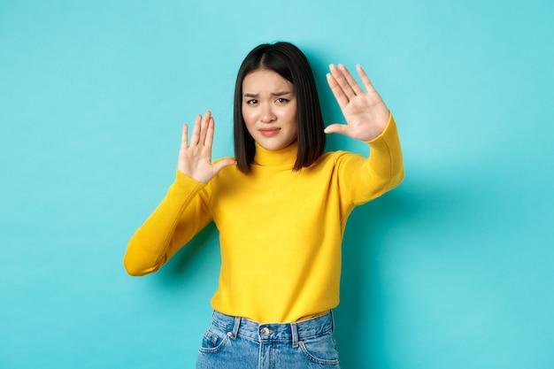 Immagine di una donna che si sente a disagio davanti alla telecamera, si copre il viso con le mani e si acciglia, implorando di smettere, in piedi contro il blu.