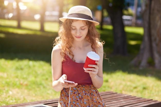 Immagine di donna con i capelli sexy seduto sulla panchina nel parco cittadino, ricarica cellulare sul banco tramite pannello solare, tenendo il caffè da asporto