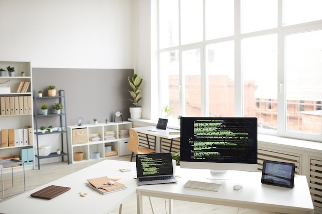Immagine del posto di lavoro con computer e tablet digitale con software sugli schermi in ufficio moderno