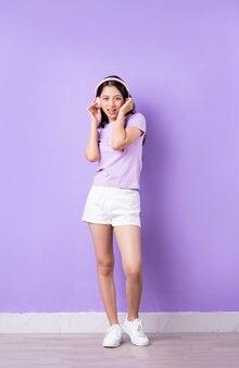 Immagine di una giovane ragazza asiatica con tutto il corpo su sfondo viola
