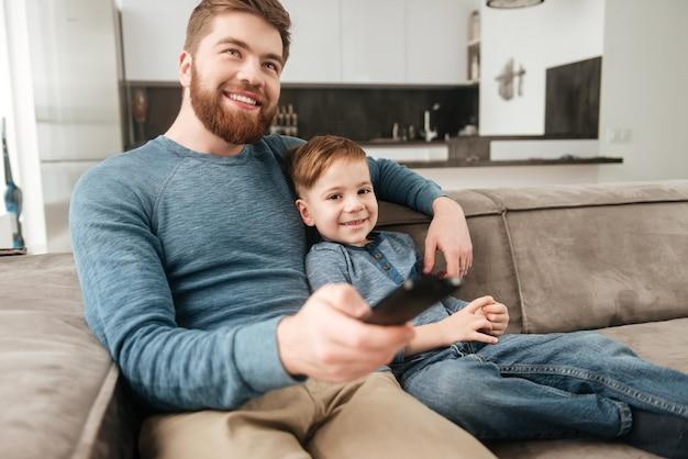 Immagine di un giovane padre barbuto che tiene il telecomando mentre guarda la tv con il suo piccolo figlio carino.