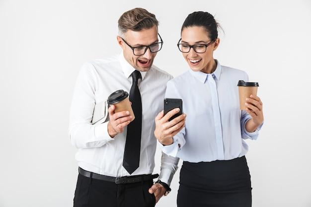 Immagine di giovani colleghi di lavoro coppia isolata sul muro bianco di bere il caffè utilizzando i telefoni cellulari.