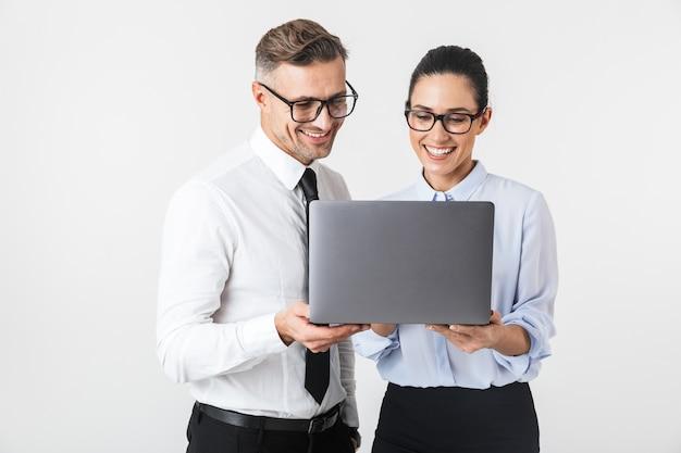 Immagine di giovani colleghi di lavoro coppia isolata sopra il muro bianco utilizzando il computer portatile.