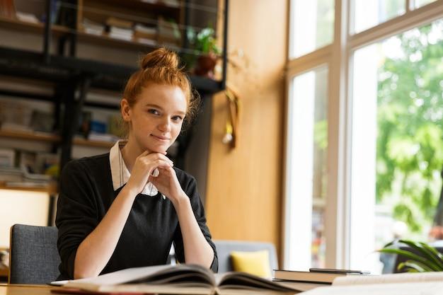 Immagine di giovane donna caucasica studiando, mentre è seduto alla scrivania in biblioteca universitaria con parete da scaffale
