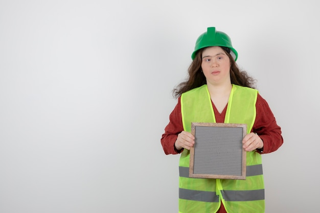 Immagine di una giovane ragazza carina con sindrome di down in piedi in giubbotto e in possesso di un telaio.