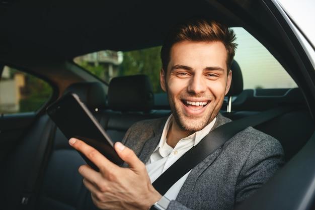 Immagine di giovane uomo regista in tuta tenendo smartphone e sorridente, mentre torna seduto in auto di business class con cintura di sicurezza