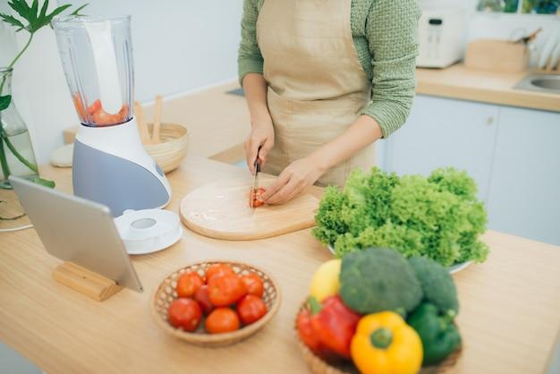 Immagine di una giovane donna in piedi in cucina che usa un tablet e cucina un'insalata di verdure