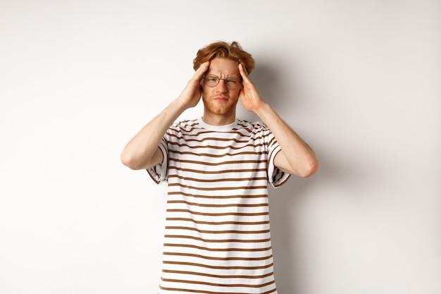 Immagine di giovane uomo con i capelli rossi e gli occhiali che tocca la testa, accigliato da dolorosa emicrania, avendo mal di testa, in piedi su sfondo bianco.