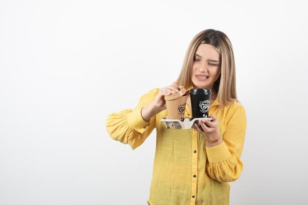 Immagine del giovane che copre i coperchi delle tazze di caffè su bianco.