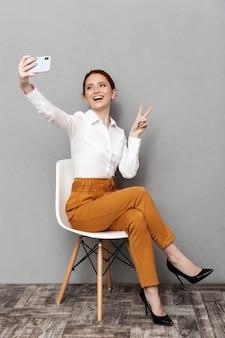 Immagine di una giovane donna d'affari dai capelli rossi 20s in abbigliamento formale utilizzando il telefono cellulare mentre è seduto su una sedia in ufficio isolato su gray
