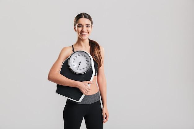 Immagine di giovane ragazza sportiva tenendo la bilancia e sorridente, isolato su muro grigio