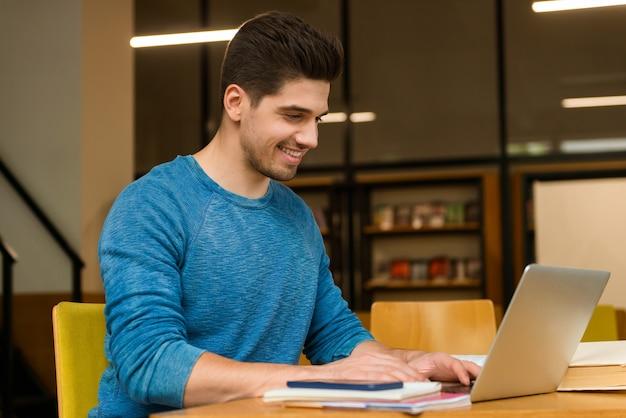 Immagine di un uomo felice giovane studente in biblioteca facendo i compiti studiando leggere e utilizzando il computer portatile.