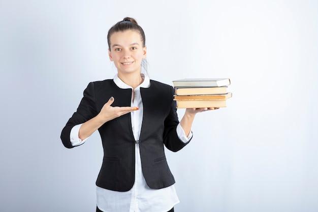 Immagine di giovane studente in possesso di libri e in piedi su bianco.