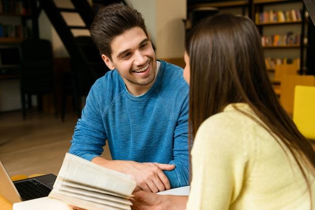 Immagine di una coppia di amici giovani studenti in biblioteca a fare i compiti studiando leggere e utilizzando il computer portatile.